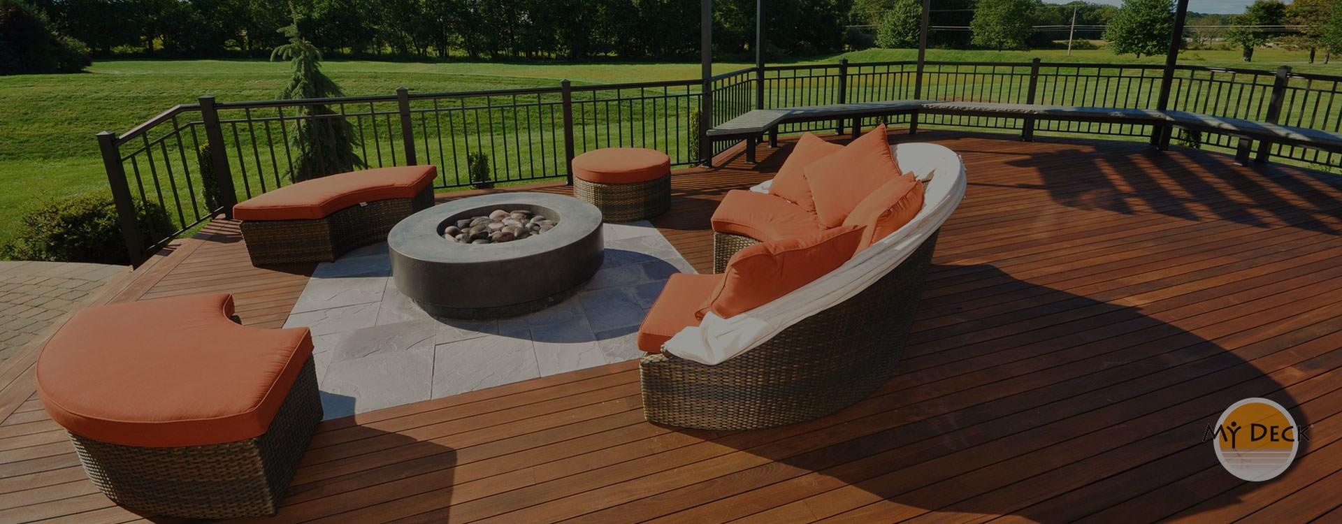 wood deck with metal railing & orange outdoor furniture around fire pit